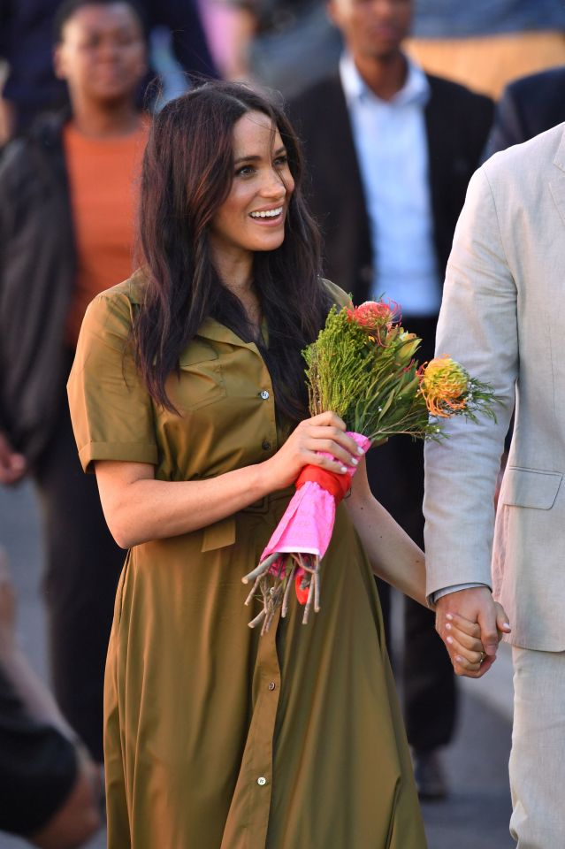 The Duchess of Sussex clutches a bouquet as she walks through the street with her husband