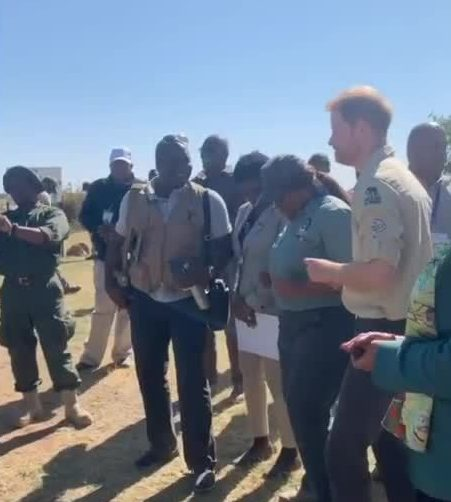 Prince Harry dances with some of the locals as he arrives in Angola