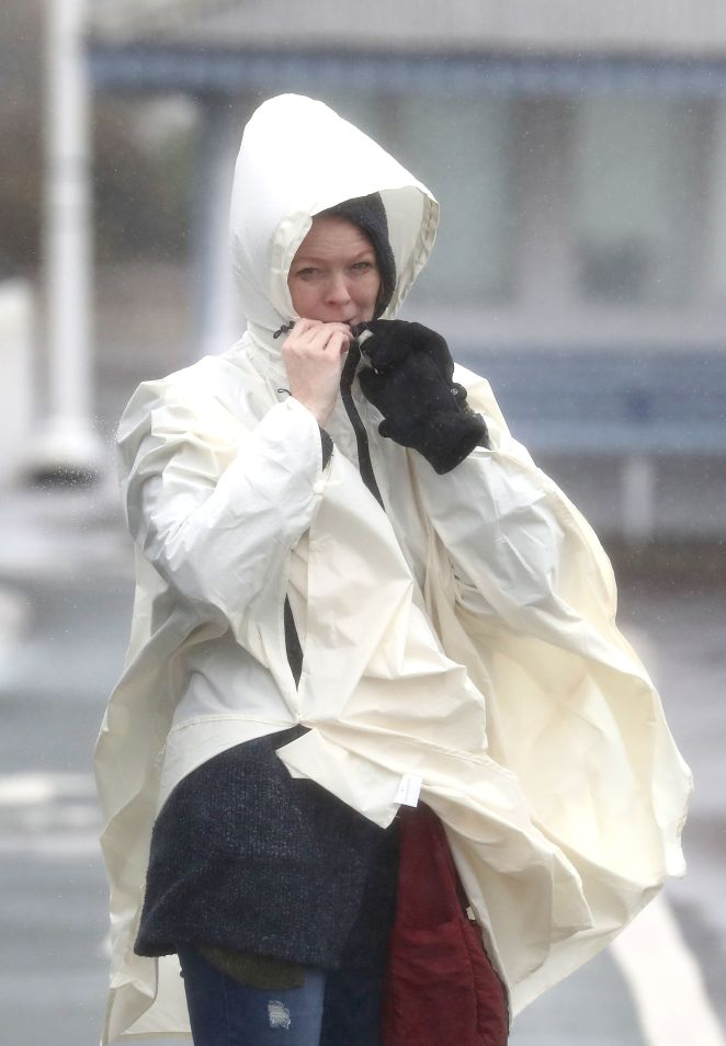 A woman wraps up against the elements on the promenade in Dover, Kent