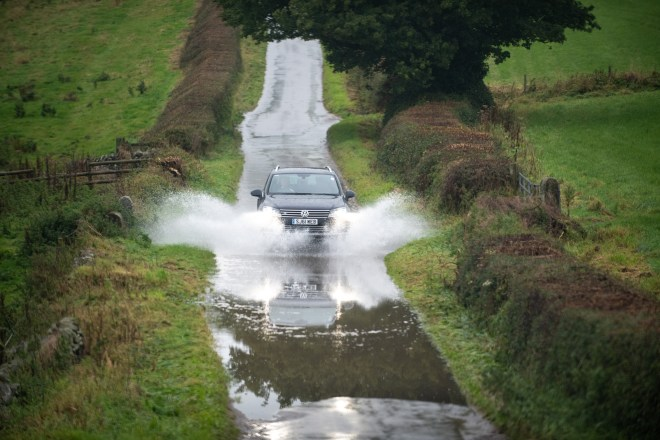A motorist drives through a flooded road in the village of Bubnell in Derbyshire this morning