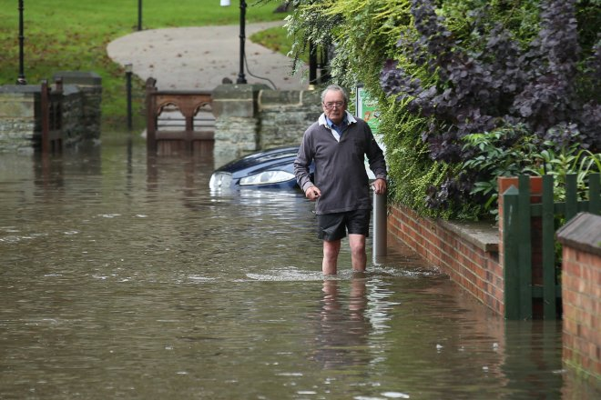 A man wades through deep flood water which has cut the village of Colston Bassett, Nottinghamshire