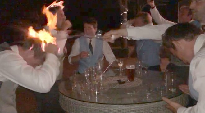 A guest splashes water on a pal's head that is on fire