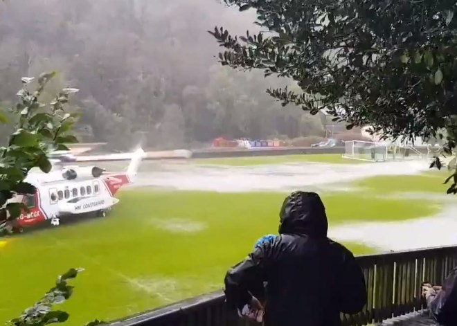A Coastguard helicopter lands on on Laxey football pitch amid flash floods in the area