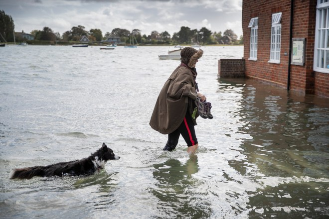 A woman and her dog wade through the water as the high tide floods the village of Bosham in West Sussex
