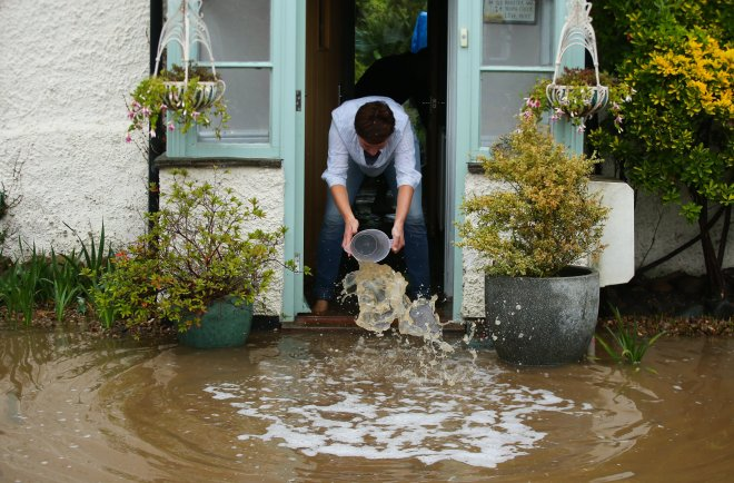 A women scoops water out her home with a bowl in Cossington, Leicestershire