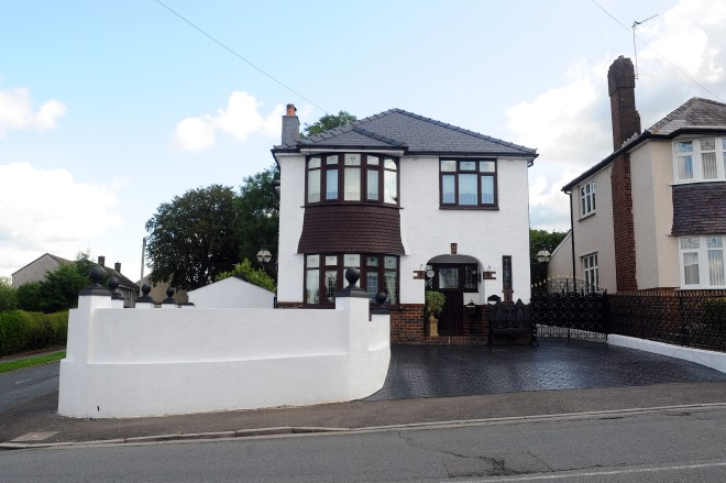 The white wall surrounds Carly's detached home in Newport
