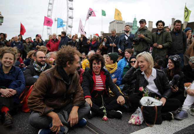 Ruby Wax and Juliet Stevenson sit together on Westminster Bridge as part of today's Extinction Rebellion protest