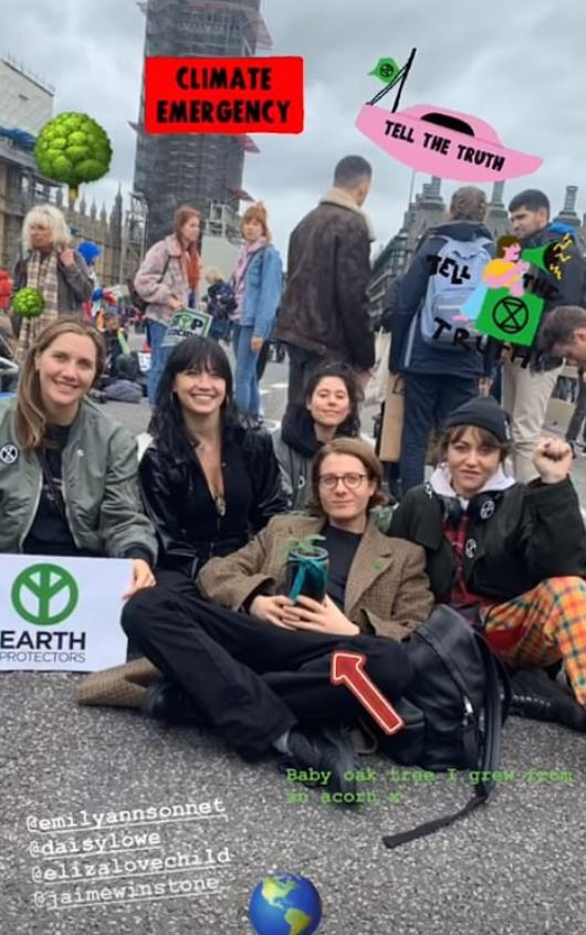 Celebrities Daisy Lowe, Jamie Winstone, Emily Sonnet sit with each other during today's Extinction Rebellion Protest