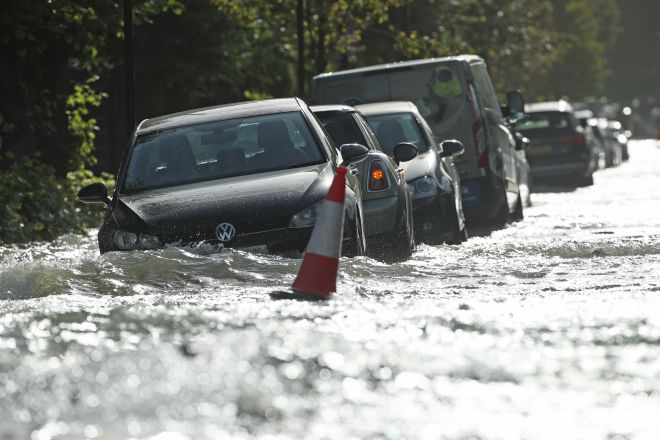 Parked cars are partly submerged in a flooded street in London earlier this week