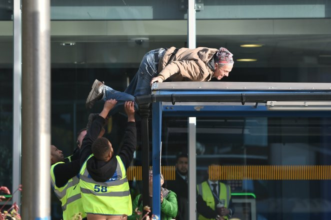 Security try to grab hold of an Extinction Rebellion protester at the airport