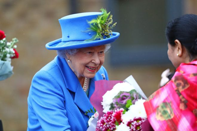 The Queen is given flowers as she arrives