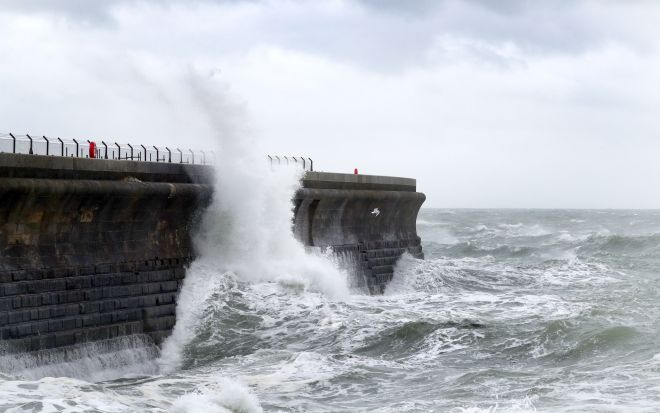 Waves crash against the harbour wall in Dover during stormy weather on Friday