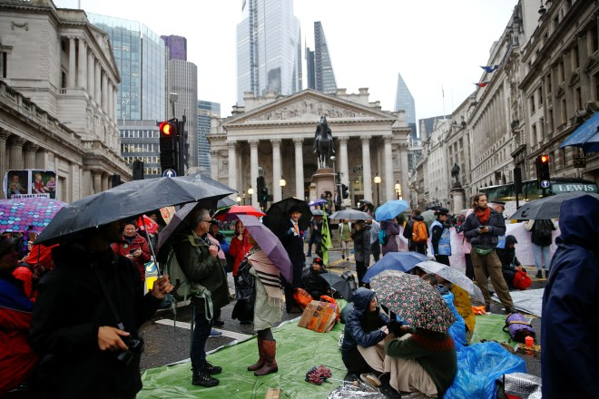Hundreds of protesters are standing outside the Bank of England in the pouring rain this morning