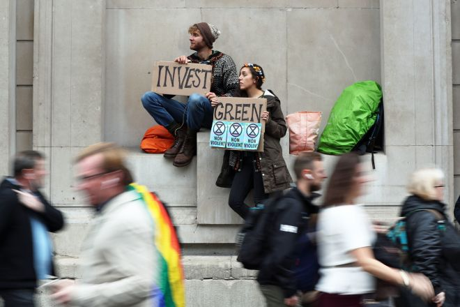 Activists hold signs during the second week of climate change protests