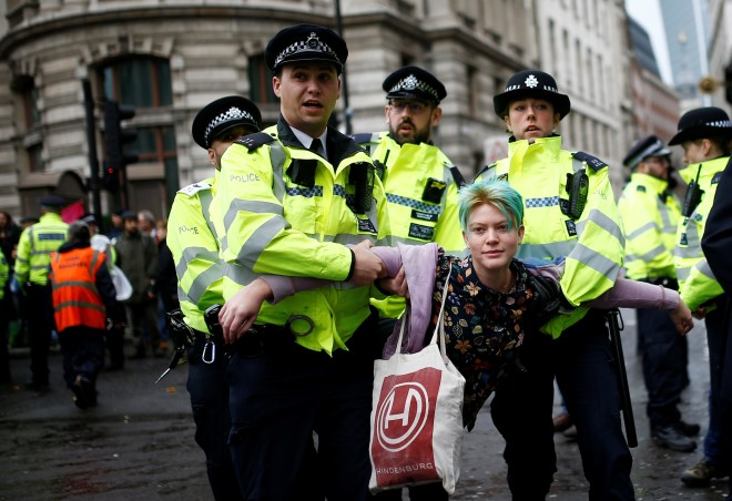 A climate change activist gets detained by police in the City of London this morning