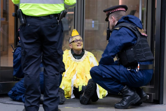 An Extinction Rebellion protester dressed as a canary remains glued on to the Walkie Talkie building this morning