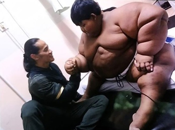 Arya, aged 10, pictured alongside Indonesian bodybuilderAde Rai at the beginning of his amazing weight loss journey