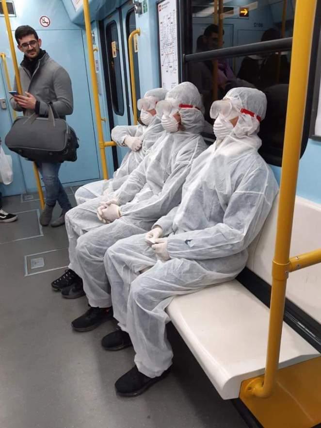 Three people wearing haz-mat style suits on the Milan metro