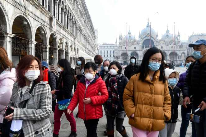 Tourists wearing protective face masks visit the Piazza San Marco, in Venice