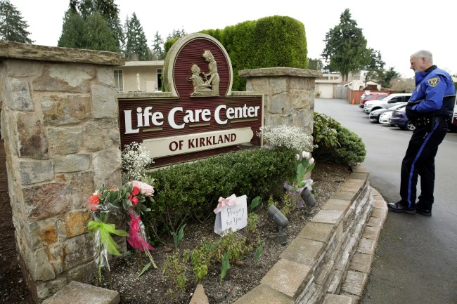 Flowers left next to the sign that marks the entrance to the car park of the Life Care Center in Kirkland