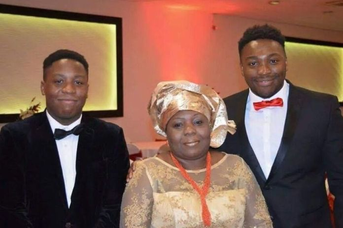 Caregiver Carol Jamabo (center) - seen with her sons Tonye Selema (left) and Abiye Selema - is believed to be the first publicly identified care worker to be publicly identified after her death with an alleged coronavirus
