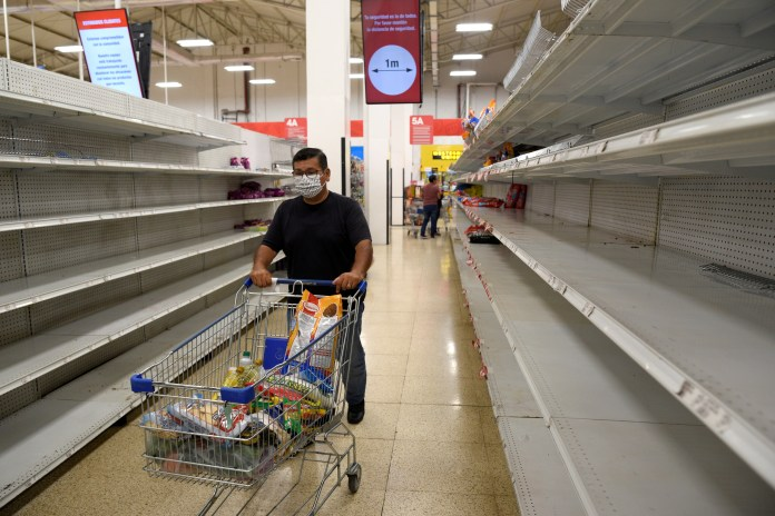A customer is seen among the empty shelves in a grocery store in Guayaquil on March 17