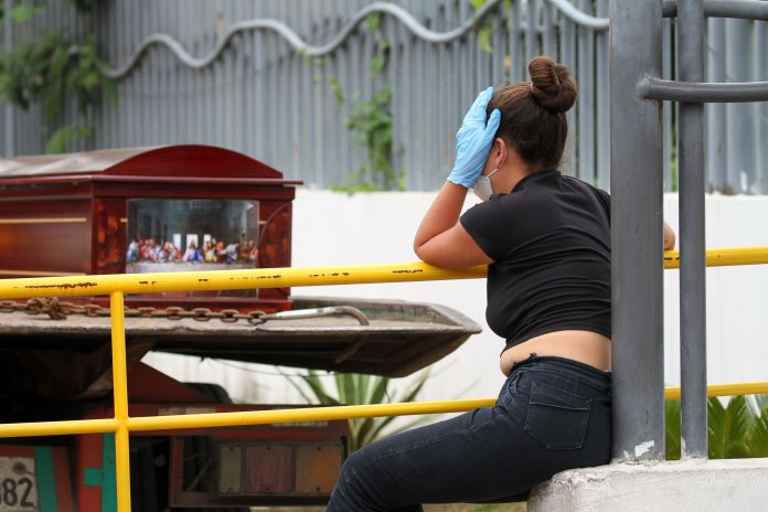 A woman wearing a mask and gloves cries by a coffin outside a hospital in Guayaquil
