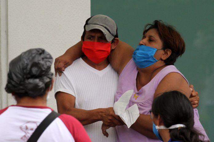 Man helps sick woman enter hospital in Guayaquil, Ecuador, April 1