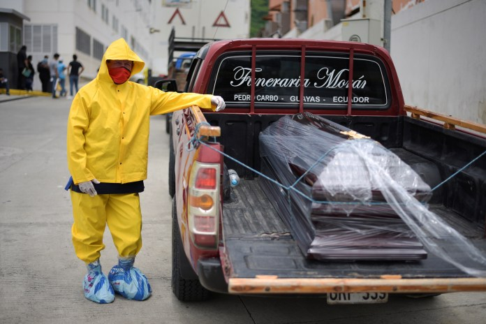 A funeral home worker in protective gear waits with a coffin on a pickup truck outside Los Ceibos Hospital in Guayaquil on April 1