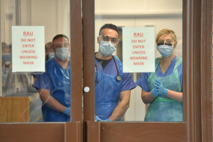Medical personnel wearing personal protective equipment (PPE) wait to receive coronavirus patients at the door of the respiratory assessment unit at Morriston Hospital in Swansea