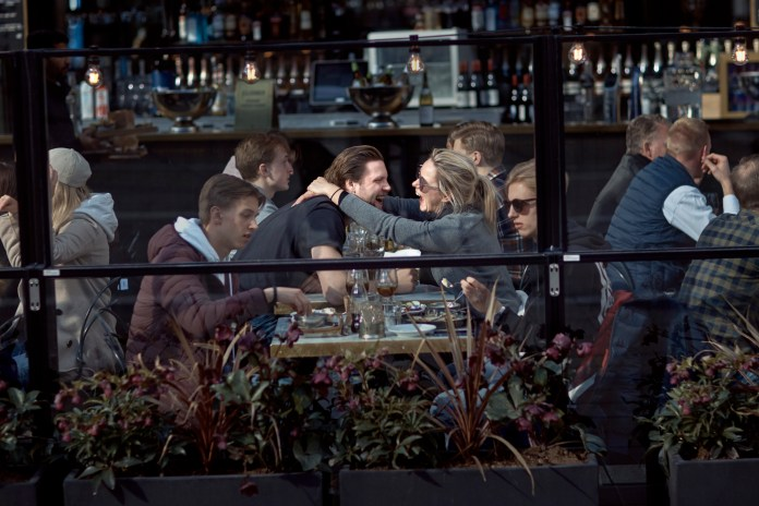 A cuddly couple in a busy restaurant in Stockholm on Saturday