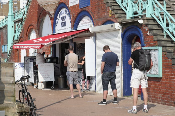 As the NHS prepares for yet more coronavirus deaths, the British stand in line at a takeout cafe on the Brighton seafront
