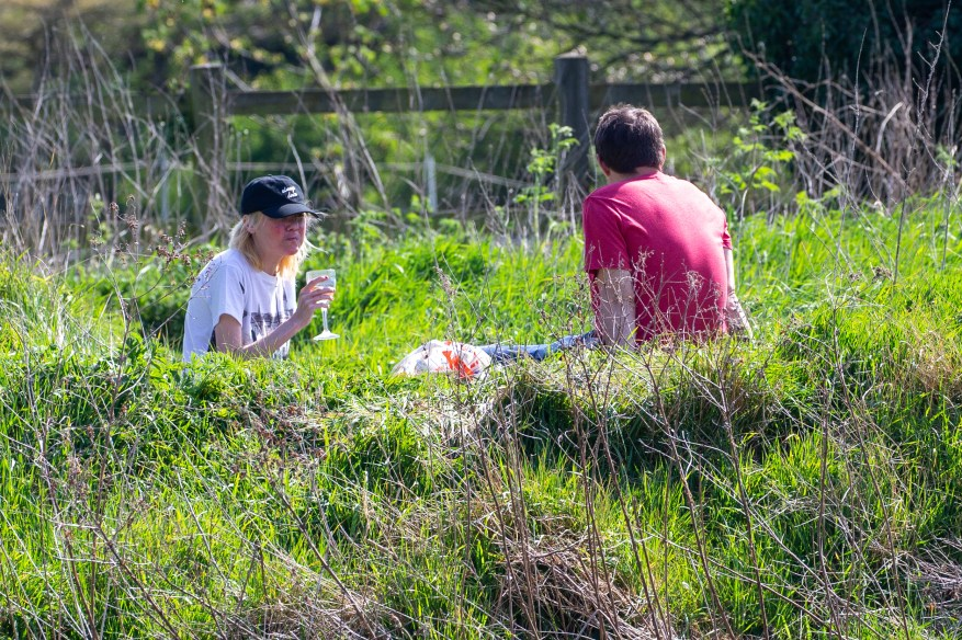 Este par se detiene para tomar una bebida alcohólica a lo largo del río Cam, Cambridgeshire, a pesar de las súplicas del gobierno y la policía de quedarse en casa