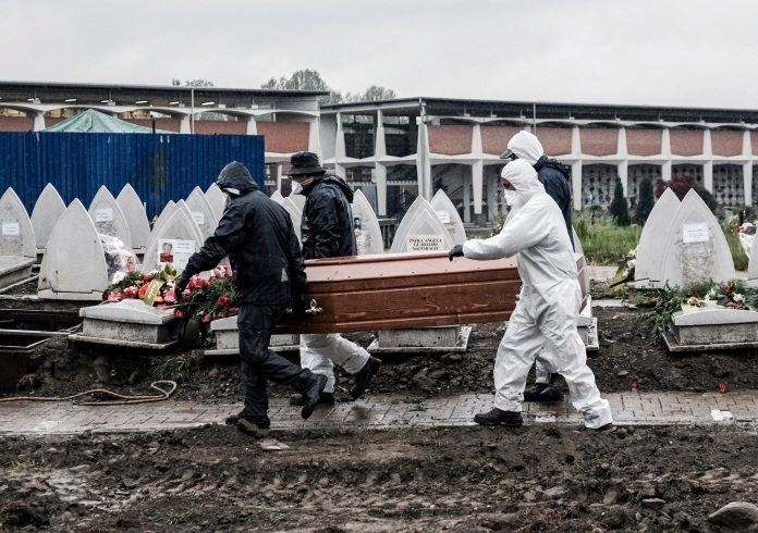 Undertaker wearing protective clothing and mask carrying a coffin to be buried, at the Monumental cemetery in Turin, Northern Italy