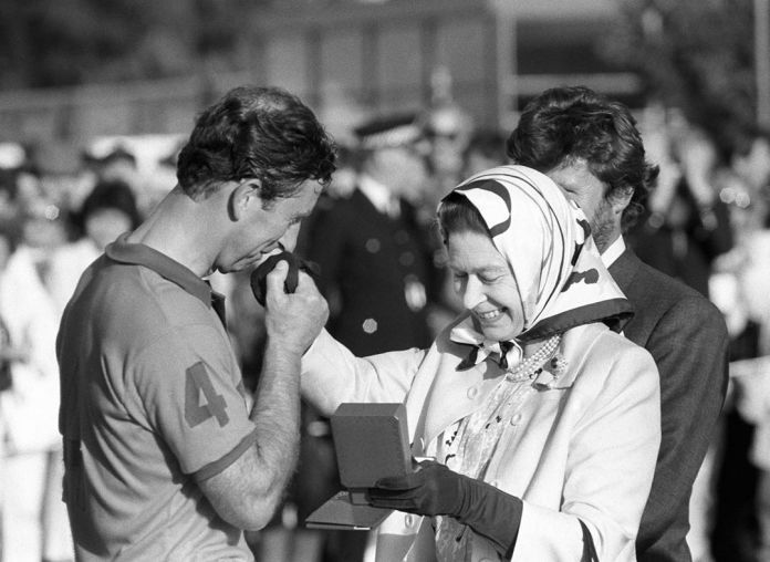 The Queen presents Prince Charles with a second prize during the Silver Jubilee Cup match against France at Windsor Great Park, 1988.