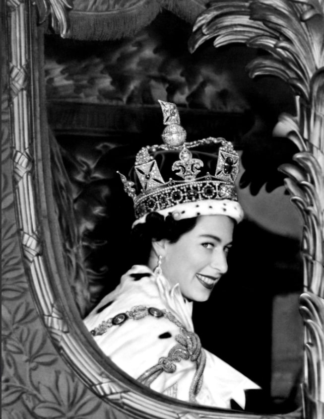 Queen Elizabeth II smiles for the crowd from her car as she leaves Westminster Abbey, London after her coronation