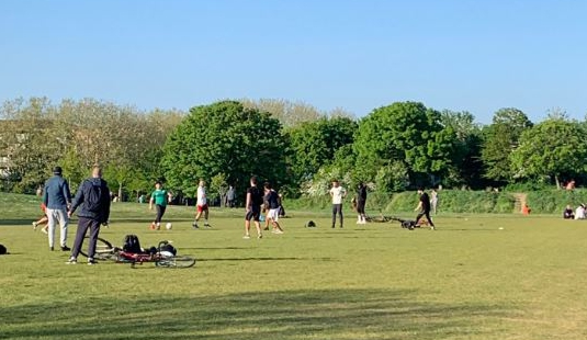 A group of men was photographed having a kickabout in a park in Southwark, when they should practice social distancing