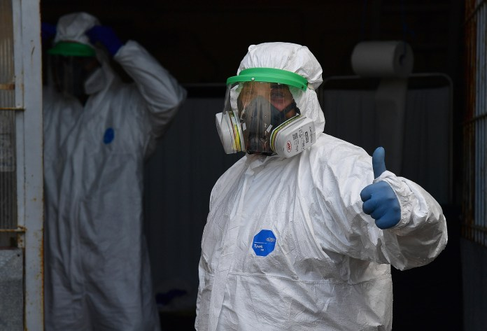 A health worker with full protective gear gives a thumbs up when they spray disinfectant as a preventative measure against the spread of coronavirus (COVID-19) at San Martino hospital in Genoa