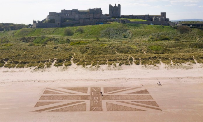 Andrew Heeley, 56, maintenance manager at Bamburgh Castle, draws a giant Union flag on the beach below Northumberland Castle
