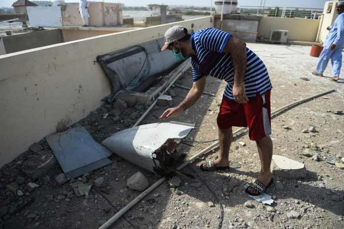 A man finds some wreckage on a rooftop in Model Colony