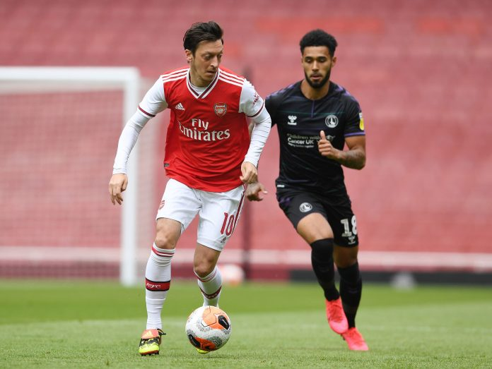 Mesut Ozil keeps the ball on Andre Green