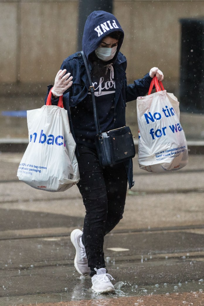 A customer runs for shelter amid heavy rain in Manchester