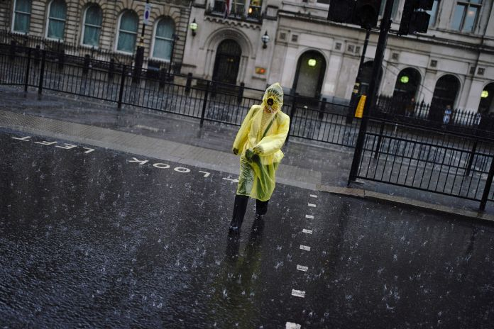 Woman walks through heavy rain in London as severe thunderstorms sweep across Britain