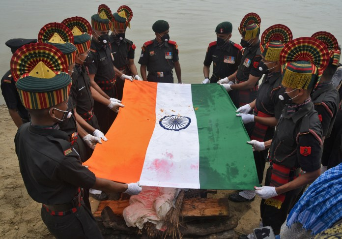Soldiers drape the Indian national flag over the body of Sunil Kumar before his cremation in Maner