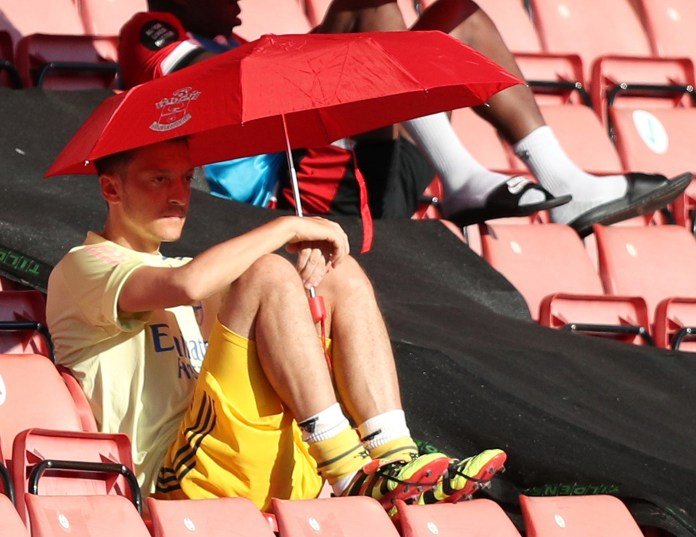 Mesut Ozil mocked by Arsenal fans for using umbrella during Southampton win… earning £1m without playing since restart