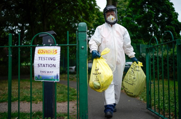 A city council worker carries rubbish from a coronavirus testing centre at Spinney Park