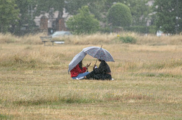 Two women take shelter under umbrellas during rain showers on Wimbledon Common