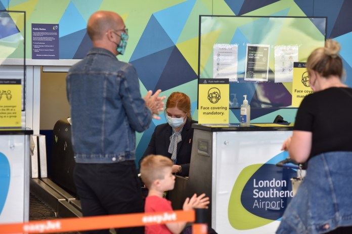 Summer is very different and expensive - a family disinfects their hands by checking their luggage before a flight