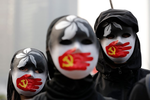 People wear masks during a rally to show support for Uighurs in Hong Kong
