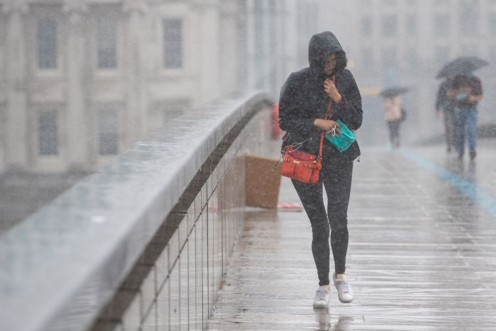 A woman runs to shelter from a heavy rain of rain on London Bridge